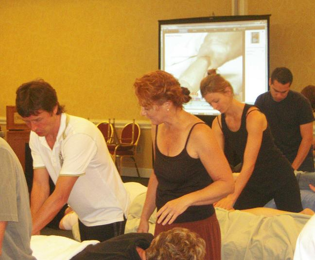 O. Bouimer individually trains a student in Sports Massage techniques while the video of each technique played on the screen